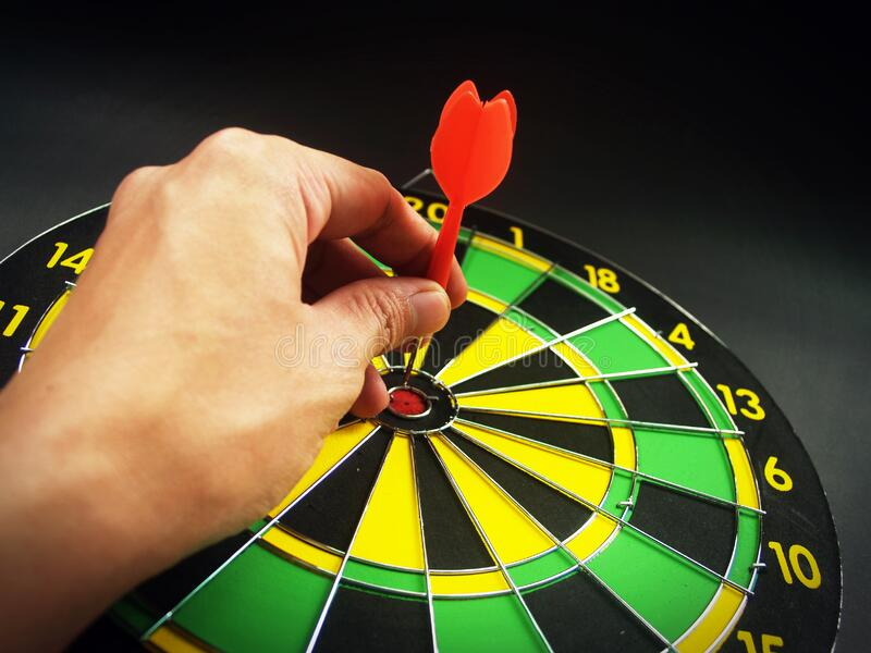 Person Holding Red Dart On Green Yellow And Black Dart Board Free Public Domain Cc0 Image