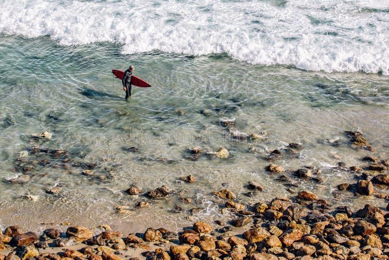 Person Holding Red Surfing Board im klaren Wasser nahe Brown-Stein während der Tageszeit lizenzfreies stockbild