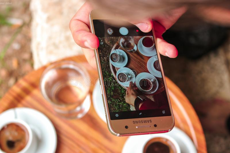 Person Holding a Samsung Galaxy Smartphone Taking a Picture on Their Coffees royalty free stock photos