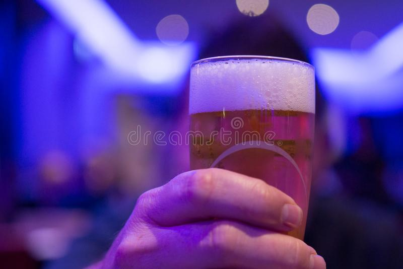 Person Holding Shot Glass Filled With Beer royalty free stock image