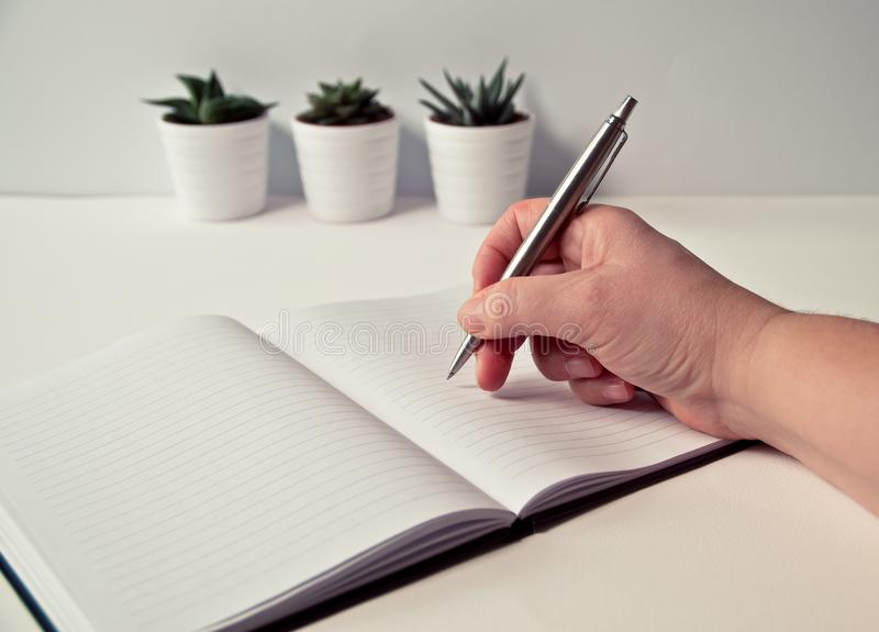Person Holding Silver Retractable Pen in White Ruled Book stock image
