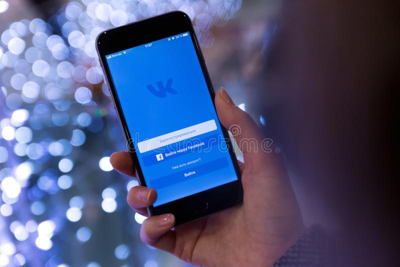 Person Holding Smartphone Displaying Vk Sign in Page royalty free stock images