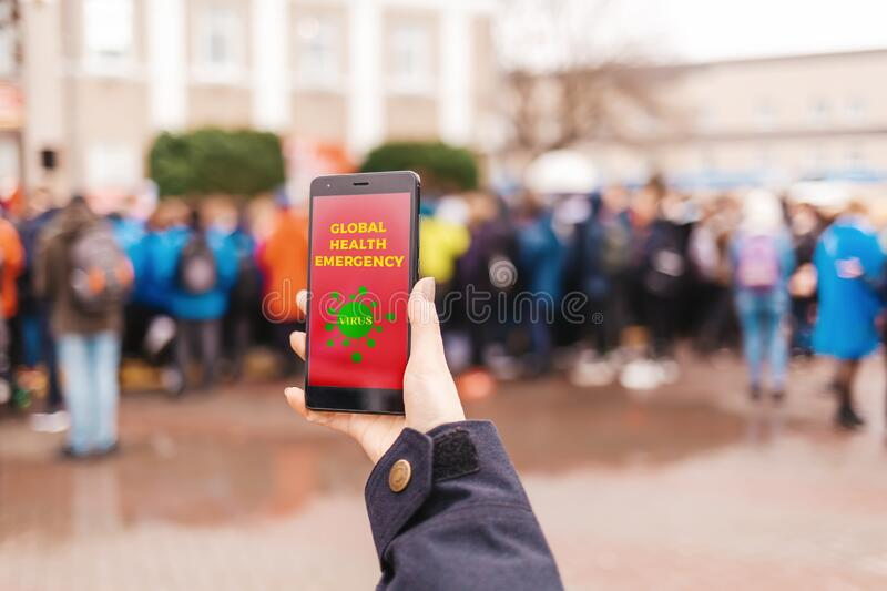 A person is holding a smartphone with the inscription Global Health emergency. In the background, a lot of people in the blur. Concept of virus royalty free stock image