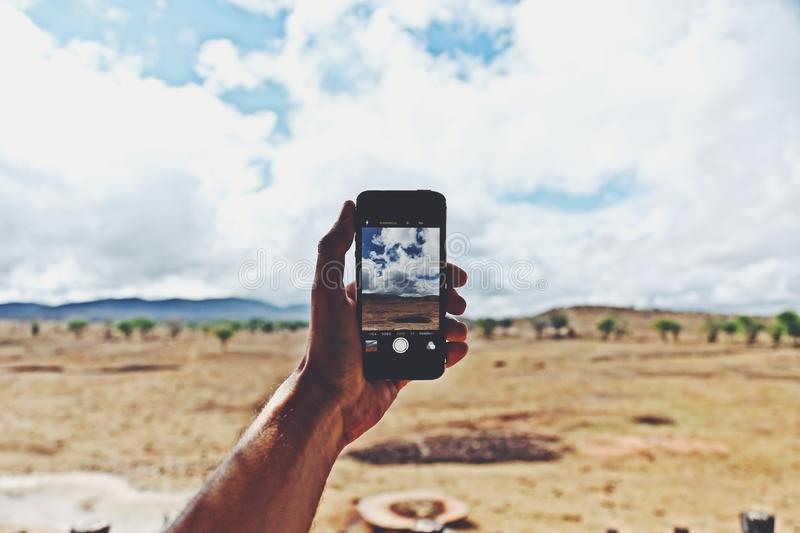 Person Holding Smartphone Showing Cloudy Sky stock photography