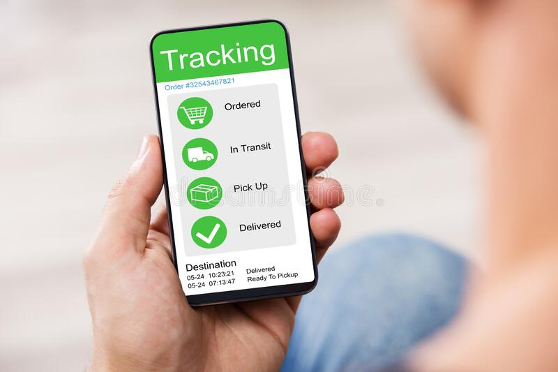 Person Holding Smartphone Showing Parcel Tracking On Screen. Defocused Person Holding Smartphone With Application Showing Parcel Tracking On Screen royalty free stock images