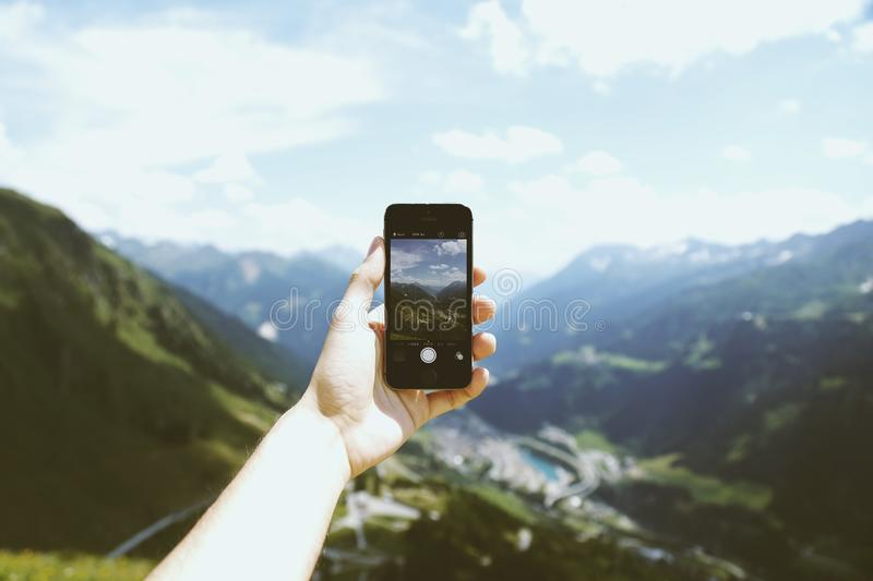 Person Holding Space Gray Iphone 5s Taking Picture of Mountains stock images