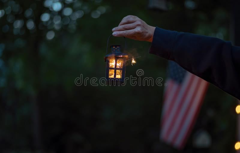 Person holding a sparkler at night on Fourth of July royalty free stock image