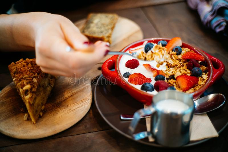 Person Holding Spoon and Round Red Ceramic Bowl With Pastries stock image