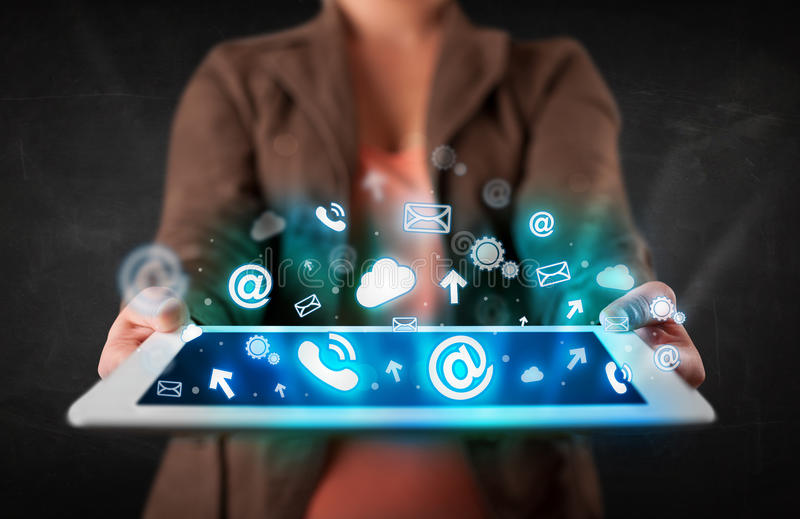 Person holding a tablet with blue technology icons and symbols stock photos