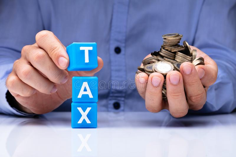 Person Holding Tax Cubic Blocks And Golden Coins stock photos