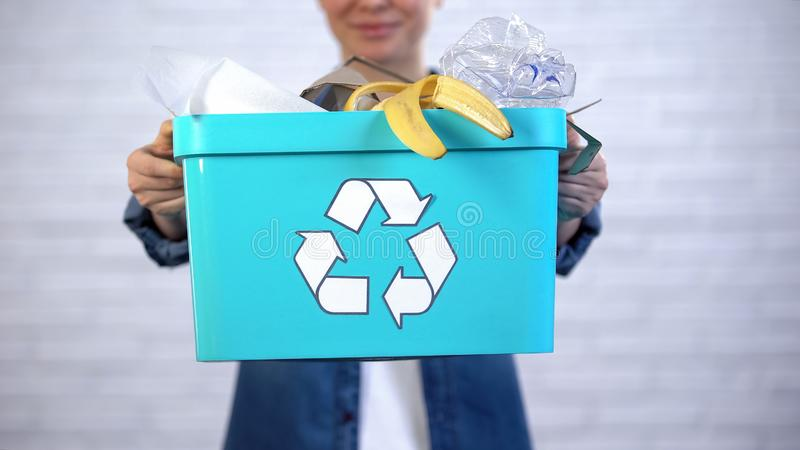 Person holding trash bin with disposable and plastic garbage, waste sorting. Stock photo stock image