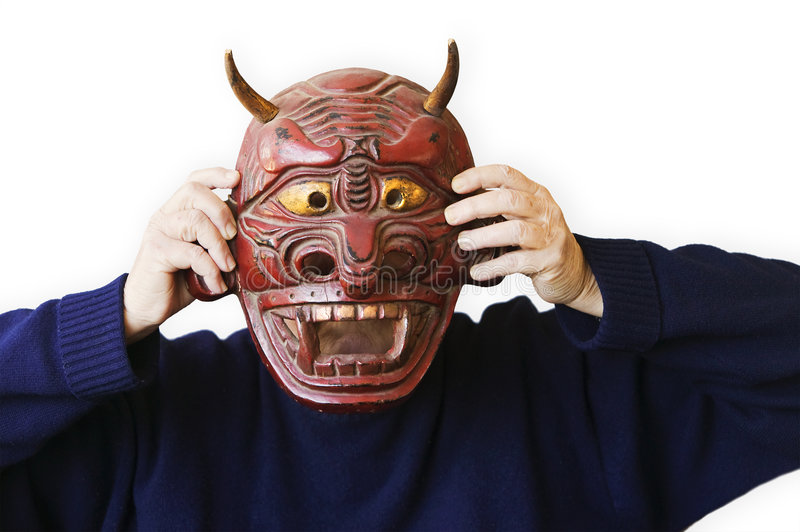 Person Holding Up A Devil Mask