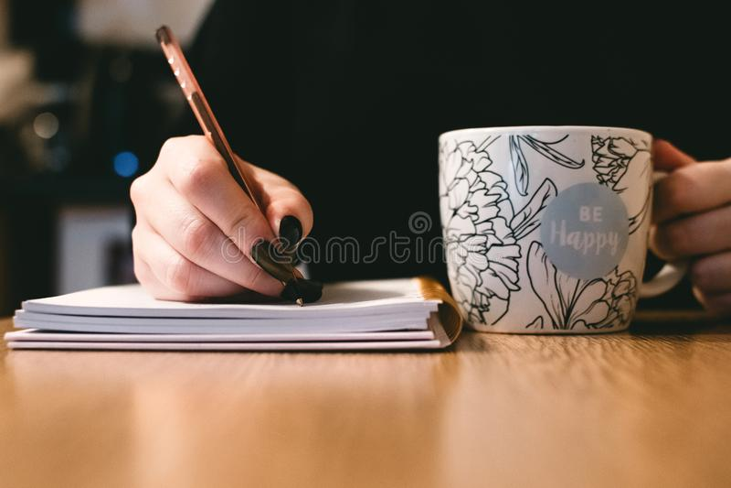 Person Holding White Ceramci Be Happy Painted Mug royalty free stock image