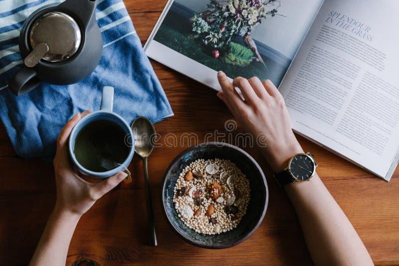 Person Holding White Ceramic Coffee-Schale, die auf Brown-Holztisch sich lehnt lizenzfreie stockfotos