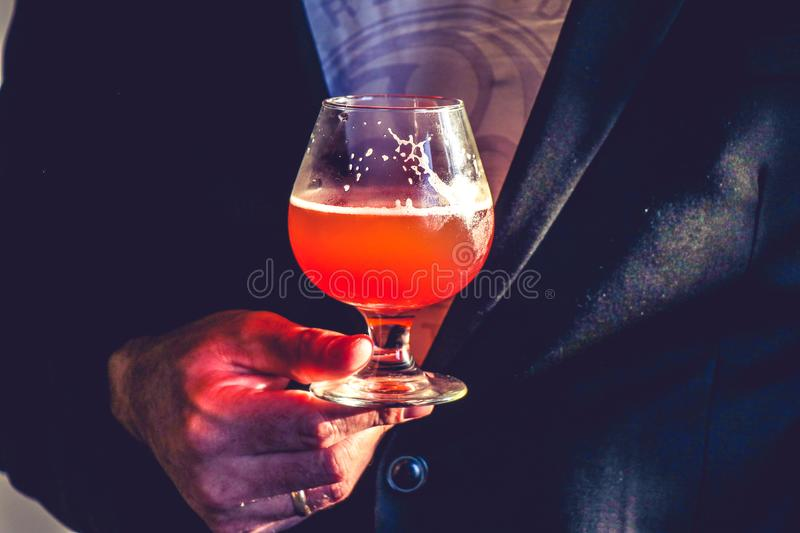 Person Holds Clear Glass Snifter With Red Beverage royalty free stock images