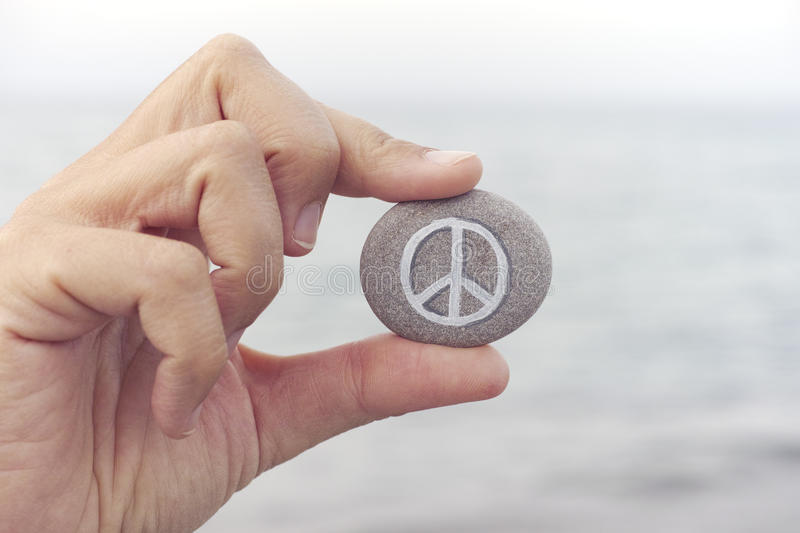 Person holds stone with peace symbol against sea in background stock image