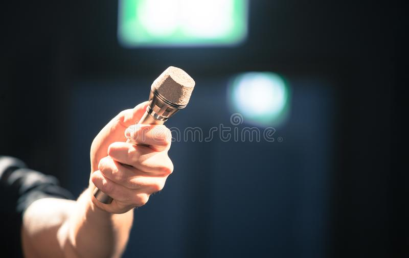 Person is holing up a microphone for an interview. Person is holding up a metal microphone and wants to interview someone, copy space journalism studio recording stock image