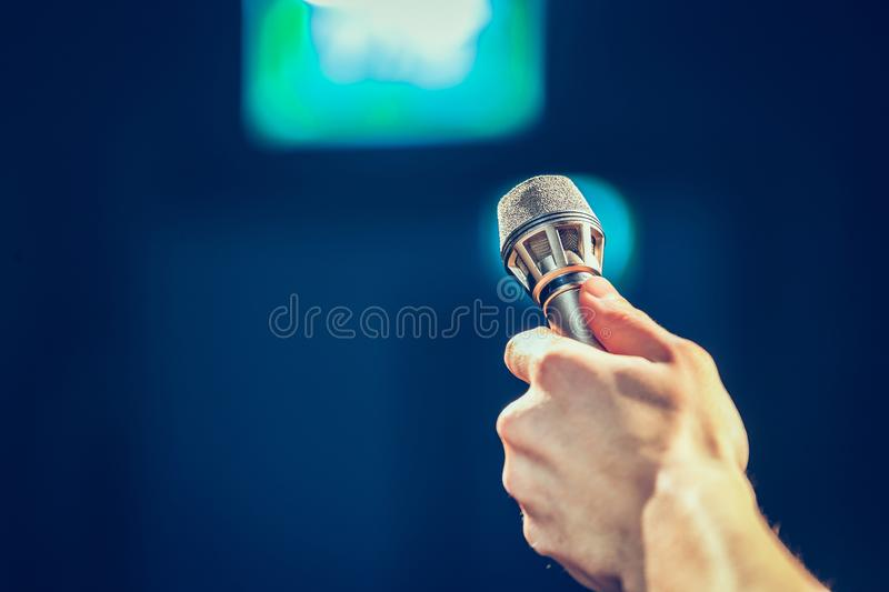 Person is holing up a microphone for an interview. Person is holding up a metal microphone and wants to interview someone, copy space journalism studio recording stock photography