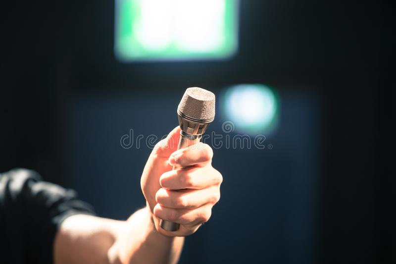 Person is holing up a microphone for an interview. Person is holding up a metal microphone and wants to interview someone, copy space journalism studio recording royalty free stock photo