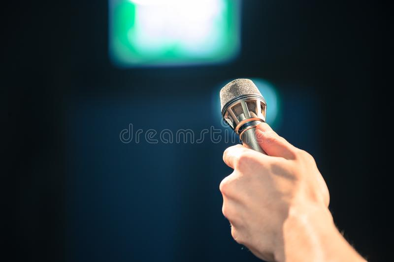 Person is holing up a microphone for an interview. Person is holding up a metal microphone and wants to interview someone, copy space journalism studio recording royalty free stock image