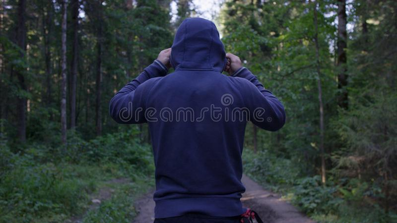 Person in a hood standing. Man in the hood in the woods. Sport in the forest on the nature.  royalty free stock photo