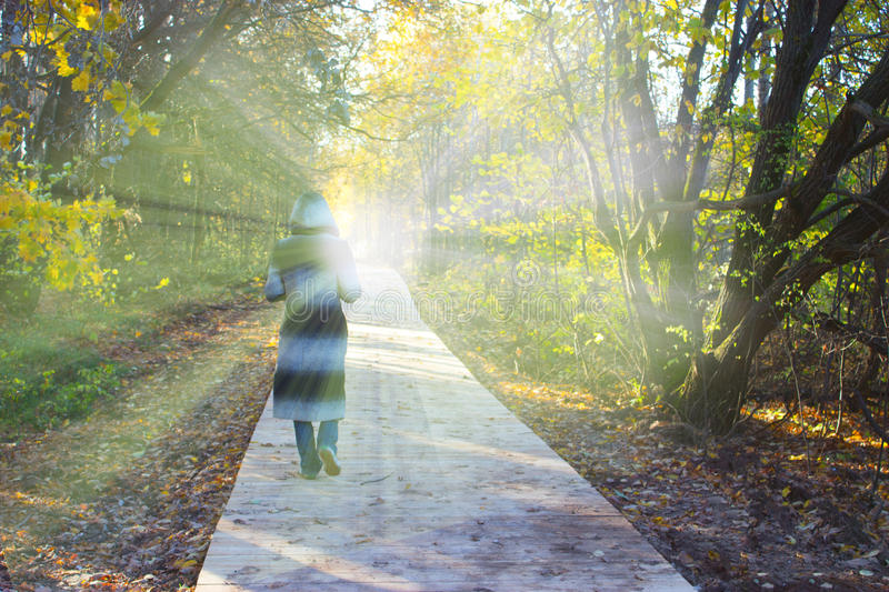 Person in a hood walking toward the light. Lidht in the end of the tunnel. clinical death concept royalty free stock photos