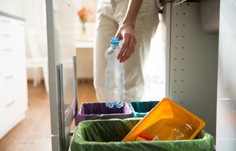 Person in the house kitchen separating waste. Man putting empty plastic bottle in recycling bin in the kitchen. Person in the house kitchen separating waste stock photos