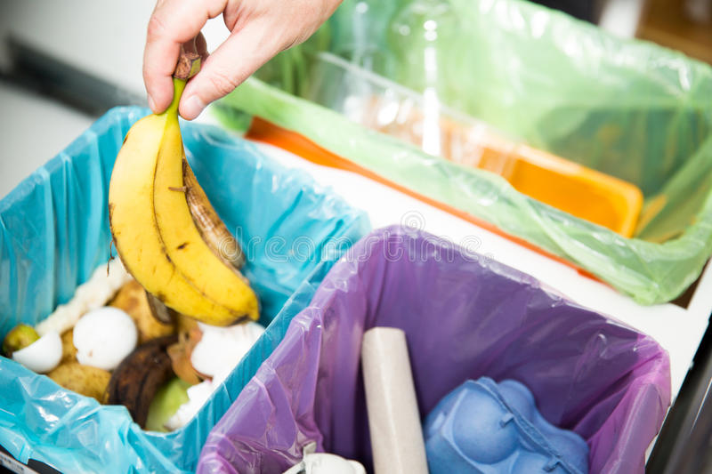 Person in the house kitchen separating waste. Woman putting banana peel in recycling bio bin in the kitchen. Person in the house kitchen separating waste royalty free stock images