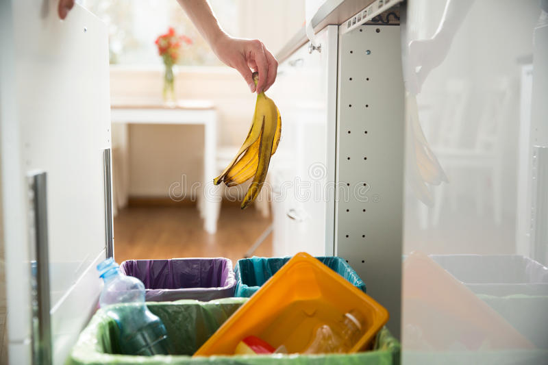 Person in the house kitchen separating waste. Woman putting banana peel in recycling bio bin in the kitchen. Person in the house kitchen separating waste stock images