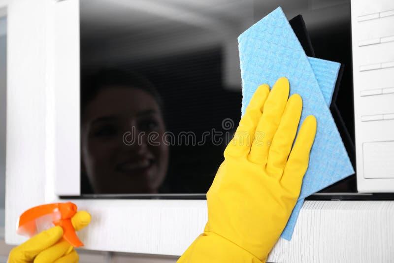 Person i handskar som gör ren mikrovågugnen, arkivfoton