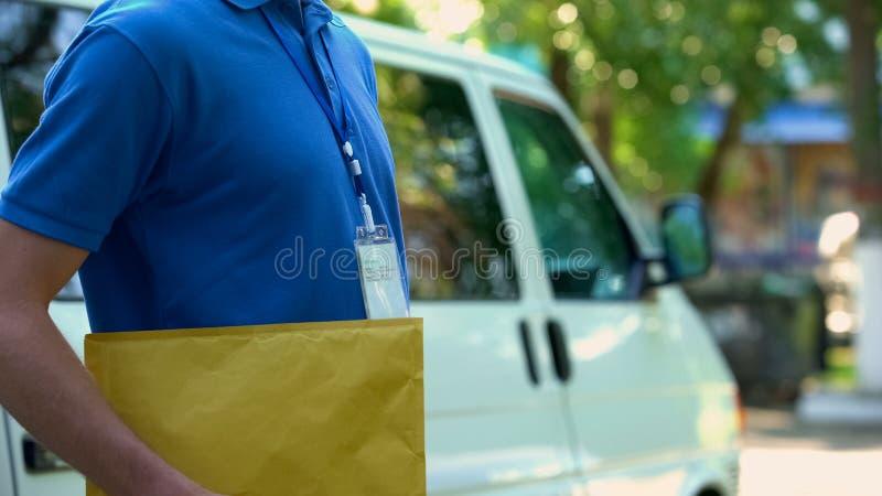 Person i likformiginnehavkuvertet med dokument, kontorsleverans, service royaltyfria bilder