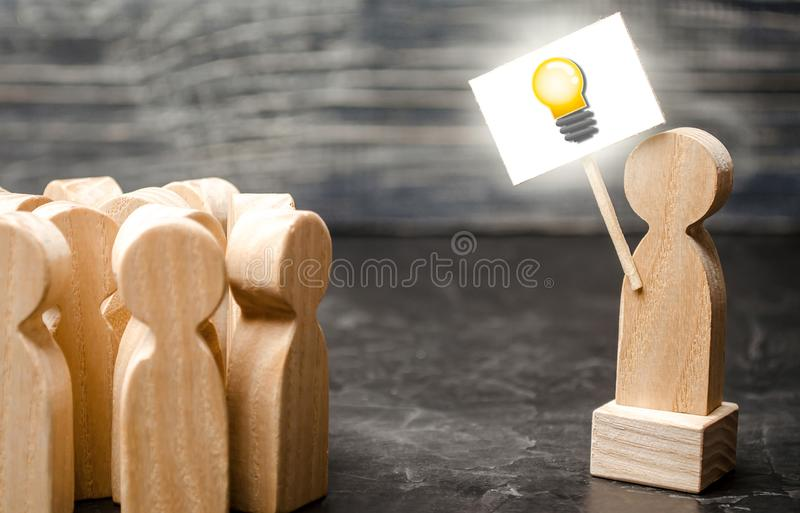 A person with an idea light bulb sign agitates a group of people. The concept of proposing new fresh ideas, finding a solution stock image
