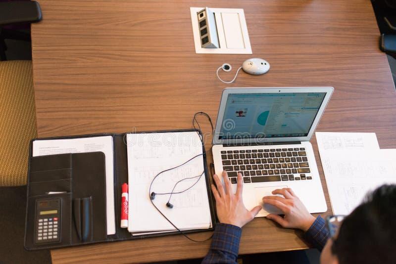 Person im blauen Smokinghemd, das weißen Laptop auf Brown-Holztisch gegenüberstellt lizenzfreie stockbilder