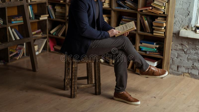Person im schwarzen Marineanzugs-Holdingbuch in seinen Händen lizenzfreie stockbilder