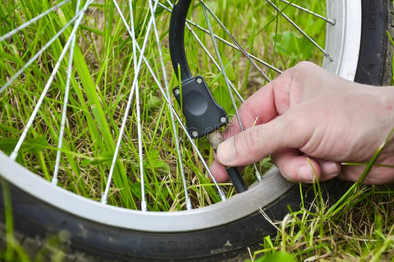 A person is inflating a bicycle wheel with the help of compressed air and a pressure gauge. Wheel and hand seen in the background royalty free stock photos