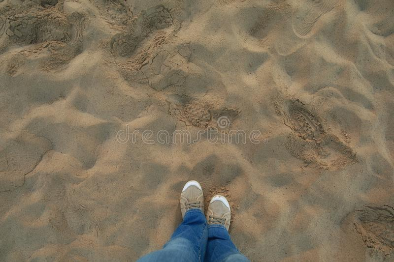 A person in jeans and sneakers stands on sunny sandy beach. Personal perspective used. stock photography