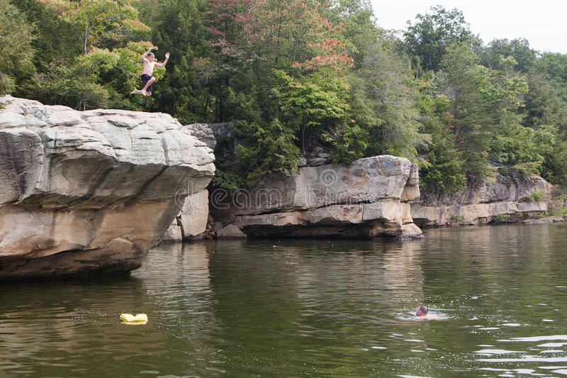 Person Jumping de falaise dans le lac images stock