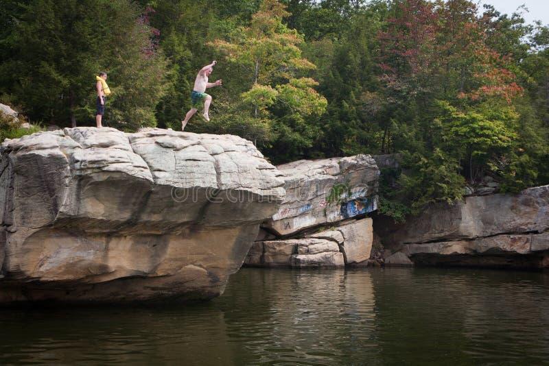 Person Jumping de falaise dans le lac photos stock