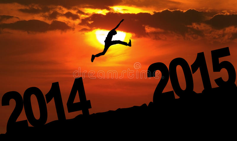 Person jumping over 2015. Silhouette person jumping over 2015 on the hill at sunset