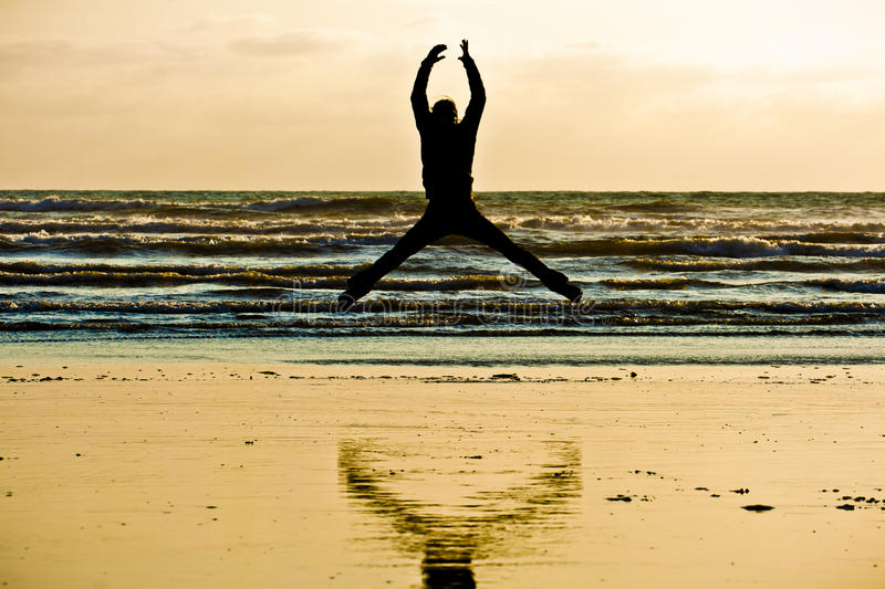 Person Jumping by the sea shore stock images