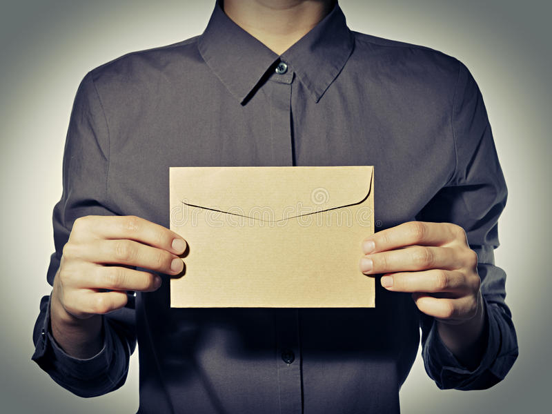 Person keeps two hands an envelope. Person (the man, the woman) keeps two hands an envelope in a gray shirt before himself stock photo