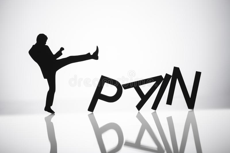Person Kicking Pain Word. Silhouette Of A Person Kicking Pain Word On Reflective Background royalty free stock photography