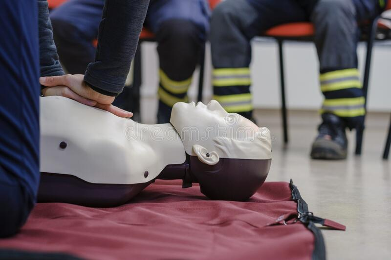 Person learning the methods of lifesaving actions by restarting the heart on a manequin. A person learning the methods of lifesaving actions by restarting the royalty free stock images