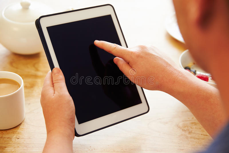 Person Looking At Digital Tablet enquanto comendo o café da manhã foto de stock royalty free