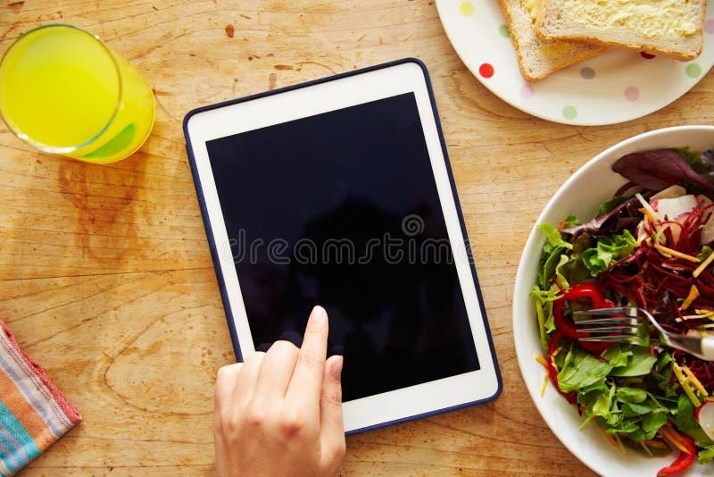 Person Looking At Digital Tablet terwijl het Eten van Lunch royalty-vrije stock foto