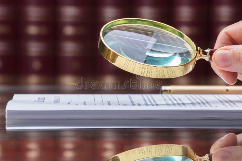Person Looking At Document With förstoringsglas royaltyfri fotografi