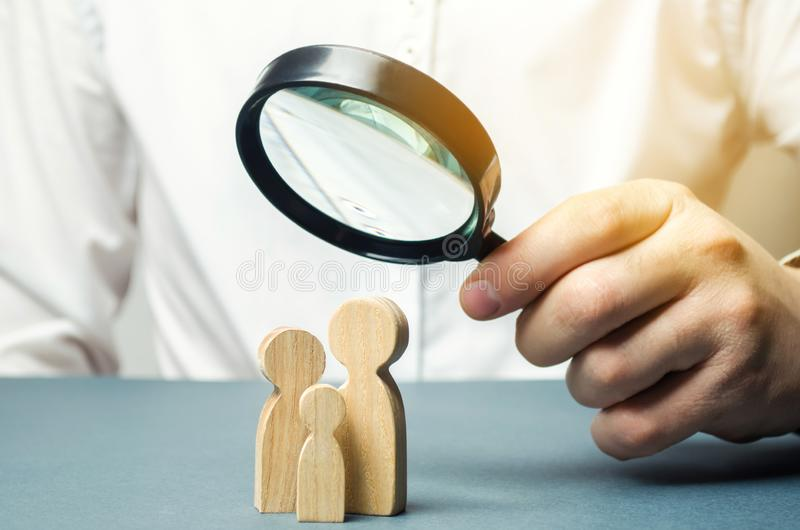 A person looks at family figures through a magnifying glass. The study of family composition, statistics. Birth control stock photography