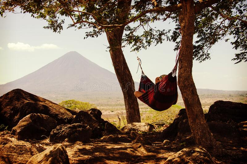 Person Lying on Black and Red Hammock Beside Mountain Under White Cloudy Sky during Daytime royalty free stock images