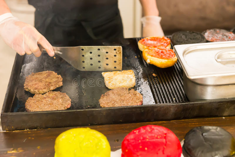 Person making hamburgers on a griddle. Grilling the beef patties and bun turning them with a spatula, close up on the hands royalty free stock photography