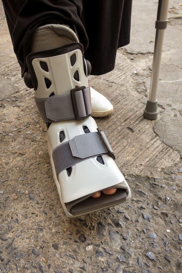 Person med den ortopediska skon och den gå pinnen royaltyfri fotografi